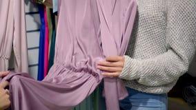 美女选择衣裳,谈话并且微笑着,当做在精品店时的购物 股票视频