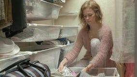 美女,一个年轻母亲在她的化装室拾起并且折叠在篮子的小孩衣服 投入事  影视素材