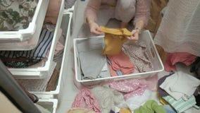 美女,一个年轻母亲在她的化装室拾起并且折叠在篮子的小孩衣服 投入事  股票视频