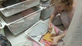 美女,一个年轻母亲在她的化装室拾起并且折叠在篮子的小孩衣服 投入事  股票录像