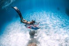 美女freediver滑动在与美国旗子的含沙海底 免版税图库摄影