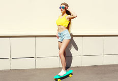 美好俏丽女孩佩带太阳镜和短裤在滑板 图库摄影