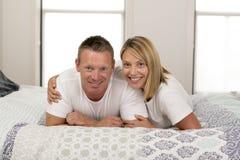 美好和光芒四射的夫妇微笑的愉快摆在的甜在家说谎在床上在成功的丈夫妻子关系概念 库存照片