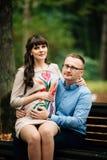 美好和愉快的怀孕的夫妇松弛外部在秋天公园坐长凳 库存图片