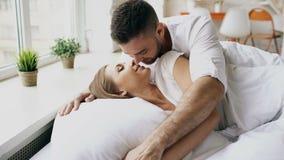 年轻美好和爱恋的夫妇在早晨醒 有吸引力的人亲吻和在床上拥抱他的妻子 股票视频