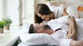 年轻美好和爱恋的夫妇在早晨醒 有吸引力的妇女亲吻和在床上拥抱他的丈夫 影视素材
