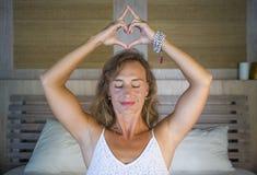 美好和适合的健康女子30s实践的瑜伽在床上在做与她的手指的凝思锻炼集中了心脏形状 免版税库存照片