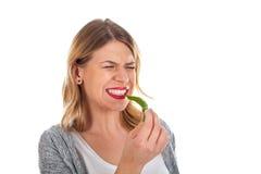 美好女孩咬住热的辣椒粉 图库摄影
