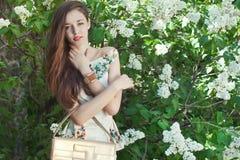 美好女孩式样摆在春天的开花的丁香附近 免版税库存图片