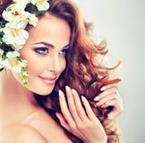 美好女孩微笑 在卷发的精美淡色花 免版税库存图片