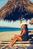 美好女性放松在日落期间sunbed的 免版税库存照片