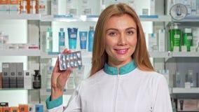 美好女性药剂师微笑,握胶囊的水泡在药房 影视素材