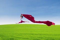 美好女性跳跃与在领域的红色围巾 免版税库存图片