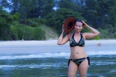 美好妇女的形状和帽子比基尼泳装在海滩放松 库存图片