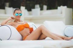 美好少妇休息的坐与一杯由游泳池的橙色鸡尾酒与在热带手段的大海 库存图片