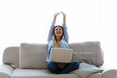 美好少妇庆祝succes,当在家时与膝上型计算机一起使用 免版税库存图片