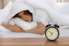 美好少妇睡觉在床上和放松早晨 一个晴天开始是时候为工作去 库存照片