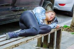 美好少妇穿着体面睡觉在一把公开椅子在公园,上瘾者概念 库存照片