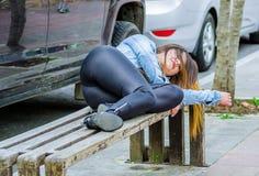 美好少妇穿着体面睡觉在一把公开椅子在公园,上瘾者概念 免版税图库摄影