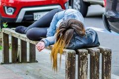 美好少妇穿着体面睡觉在一把公开椅子在公园,上瘾者概念 图库摄影