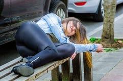 美好少妇穿着体面睡觉在一把公开椅子在公园,上瘾者概念 免版税库存图片