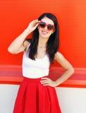 美好微笑的深色妇女佩带红色太阳镜和裙子在五颜六色 库存图片