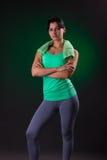 美好微笑运动,健身妇女身分,摆在与在灰色背景的一块毛巾与绿色背后照明 库存图片