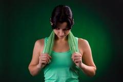 美好微笑运动,健身妇女身分,摆在与在灰色背景的一块毛巾与绿色背后照明 库存照片