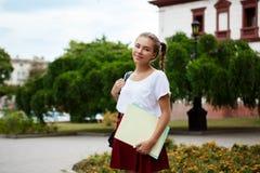 年轻美好快乐女学生微笑,拿着文件夹户外,公园背景 免版税图库摄影