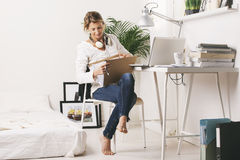 美好成熟的商业妇女搜寻在书桌上的文件。 图库摄影