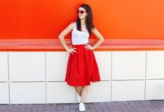 美好深色妇女佩带太阳镜和红色裙子在城市 免版税库存照片