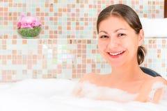 美好深色微笑在极可意浴缸 库存照片