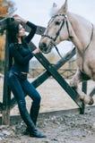 美好深色摆在与一匹马在国家大农场的秋天下午 生活方式照片 床单方式放置照片诱人的白人妇女年轻人 马背ridin 免版税库存照片