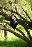 美好深色摆在公园 一名无忧无虑的妇女的画象一件黑礼服的 库存图片