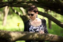 美好深色摆在公园 一名无忧无虑的妇女的画象一件黑礼服的 免版税图库摄影
