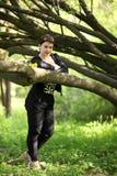 美好深色摆在公园 一名无忧无虑的妇女的画象一件黑礼服的 图库摄影