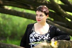 美好深色摆在公园 一名无忧无虑的妇女的画象一件黑礼服的 免版税库存图片