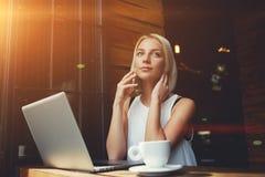 美好白肤金发女性谈话在手机,当休息在便携式计算机上时的工作以后 库存图片