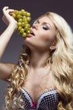 年轻美好白肤金发摆在用葡萄,演播室射击 免版税库存图片