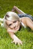 美好白肤金发放松在草 库存照片