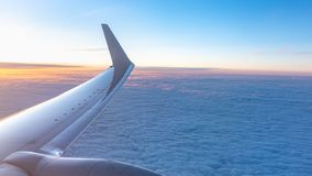 美好的三文鱼黎明和一架飞机的翼在云彩上的 库存照片