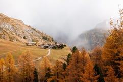 美好的与许多老瑞士山中的牧人小屋的秋天高山风景在策马特地区 免版税库存图片