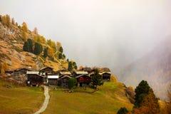 美好的与许多老瑞士山中的牧人小屋的秋天高山风景在策马特地区 免版税库存照片