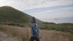 美好的中部变老了在惊人的大瑟尔海洋岩石海岸线的妇女步行与大山,对照相机微笑  股票视频