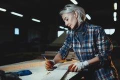 美好的中部年迈的妇女木匠设计师在树与统治者一起使用,做山谷在车间 现代阴物的图象 免版税库存照片