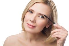 美好的中部应用眼眉胶凝体的年迈的妇女 免版税图库摄影