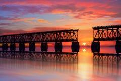 美好的五颜六色的日落或日出与残破的桥梁和多云天空 免版税库存照片