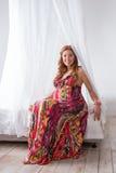 年轻美好的五颜六色的礼服的时尚孕妇坐床 免版税库存照片