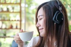 美好的亚洲妇女关闭她的眼睛和听到与耳机的音乐,当喝与感到的咖啡愉快时和放松  库存图片