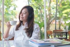 美好的亚洲妇女关闭她的眼睛和听到与耳机的音乐,当喝与感到的咖啡愉快时和放松  免版税库存照片